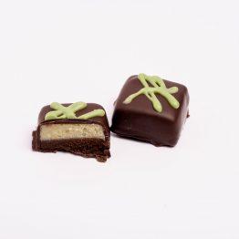 Umplutura in doua straturi din ciocolata neagra si pasta de fistic si ciocolata alba cu matcha pudra, inrobata in ciocolata neagra 54% cacao, decorata manual cu ciocolata alba si matcha