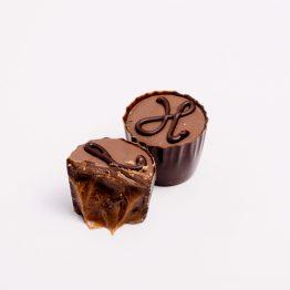 Umplutura din caramel, ciocolata cu lapte si cafea concentrata in ciocolata neagra 54% cacao, decorata manual cu ciocolata neagra